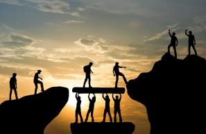 Group of people on peak mountain climbing helping team work , travel trekking success business concept Credit: iStock/ LoveTheWind